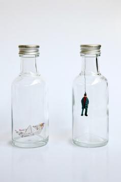 """Thais Guglielme . Sem título, 2013. Série """"Il me semble que je serais toujours bien la ou je ne suis pas"""" . garrafa, boneco de chumbo e papel. 3,5 x 10 cm"""