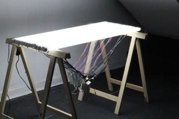 "Leonardo Stroka . ""Mesa"", 2014 . lâmpada fluorescente e cavalete . 85 x 125 x 75 cm"