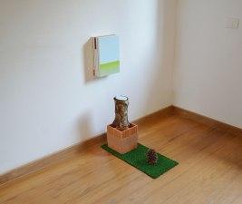 Carlos Medina, Escamas, 2016. Acrílico, tela, madeira, tijolos, pinha e grama sintética. 70x70x25cm