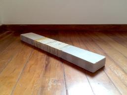 Marcelo Barros. Pensamentos-chão, 2016. Série: Poemas Sólidos. Lombadas de livros recortadas e tijolos refratários. 100 X 12 X 5 cm